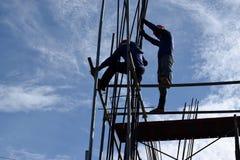 Due lavoratori dell'industria siderurgica della costruzione filippina che montano le barre d'acciaio su grattacielo senza i vesti immagini stock libere da diritti