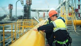 Due lavoratori di pianta in uniforme che fa misura della dimensione del tubo d'acciaio facendo uso del rotolo del nastro di misur archivi video