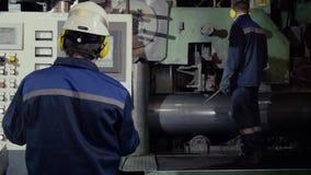 Due lavoratori in impianto di produzione come gruppo che discute, scena industriale nel fondo Lavoratore due in fabbrica sulla ma archivi video