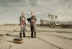Due lavoratori nel giacimento di petrolio Fotografie Stock Libere da Diritti