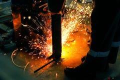 Due lavoratori saldano la parte di metallo in un'officina nel luogo di lavoro Scintille di saldatura luminose immagini stock