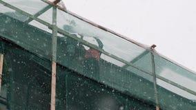 Due lavoratori stanno sull'armatura della costruzione e gettano la neve dal tetto video d archivio