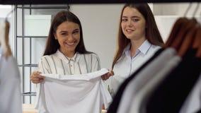 Due lavoratrici del deposito di modo che discutono abbigliamento sull'esposizione immagini stock