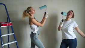 Due lavoratrici facendo uso del rullo per dipingere le pareti nell'appartamento o nella casa Costruzione, riparazione e rinnovame archivi video