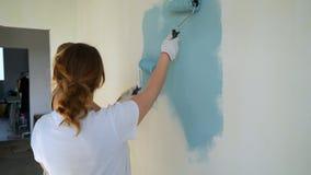 Due lavoratrici facendo uso del rullo per dipingere le pareti nell'appartamento o nella casa Costruzione, riparazione e rinnovame stock footage