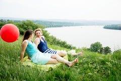 Due le migliori ragazze che si siedono sull'erba Fotografie Stock