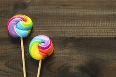 Due lecca-lecca colorate arcobaleno su fondo di legno blu Immagini Stock