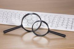 Due lenti d'ingrandimento con una tastiera di computer Immagini Stock Libere da Diritti
