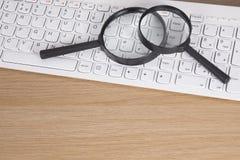 Due lenti d'ingrandimento su una tastiera di computer Fotografie Stock Libere da Diritti