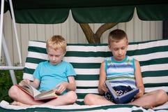 Due libri di lettura dei fratelli all'aperto Fotografia Stock