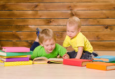 Due libri di lettura dei fratelli piccoli all'interno Fotografia Stock