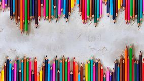 Due linee di Pecils dei colori differenti sul fondo grigio del cemento in composizione verticale, bambino, bambini, istruzione, a immagine stock