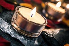 Due lumi di candela romantici sull'ardesia con Rose Petals And Leafs Fotografia Stock Libera da Diritti