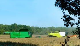 Due macchine agricole funzionano nel campo, mietitrici del grano funzionano nel campo, terreno agricolo Fotografia Stock Libera da Diritti
