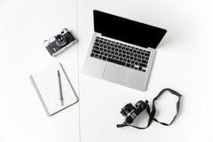 Due macchine fotografiche, blocco note con la penna e computer portatile dello schermo in bianco Immagine Stock