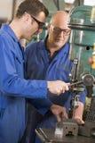 Due macchinisti che lavorano alla macchina Fotografia Stock