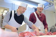 Due macellai che preparano carne in negozio immagini stock
