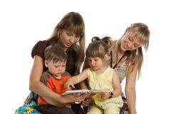 Due madri hanno letto i libri ai loro bambini Immagini Stock Libere da Diritti