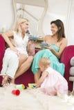 Due madri in salone con i bambini ed il caffè fotografia stock