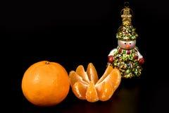 Due mandarini e figure di una fine del pupazzo di neve su isolati sul nero Fotografia Stock Libera da Diritti