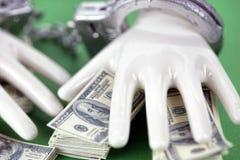 Due mani ceramiche bianche con le manette su un mucchio di 100 note del dollaro Fotografie Stock Libere da Diritti