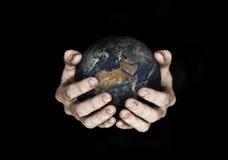 Due mani che giudicano pianeta Terra isolato sul nero Elementi di questa immagine ammobiliati dalla NASA Immagini Stock