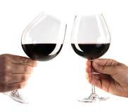 Due mani che incoraggiano con i vetri di vino rosso fotografia stock