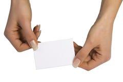 Due mani che mantengono una scheda in bianco fotografia stock