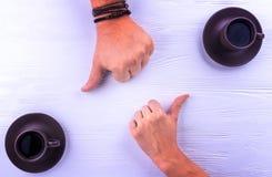 Due mani che mostrano i pollici su per un caffè Fotografie Stock Libere da Diritti
