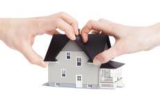 Due mani che provano a dividere casa, isolata immagine stock