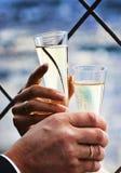 Due mani che tengono il champagne di cerimonia nuziale Fotografia Stock