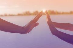 Due mani che tengono il mare di puzzle ed il bello Fotografia Stock