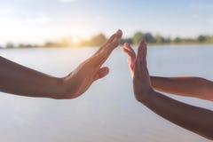 Due mani che tengono il mare di puzzle ed il bello Immagine Stock Libera da Diritti