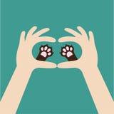 Due mani che tengono la stampa sveglia della zampa del cane del gatto Animali da compagnia di cura e di amore Concetto della mano Fotografia Stock