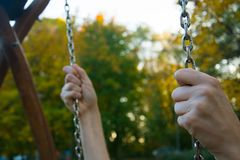 Due mani che tengono strettamente le catene del bambino oscillano Immagine Stock