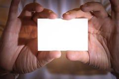 Due mani che tengono un biglietto da visita in bianco immagini stock libere da diritti