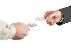 Due mani che vengono dalle direzioni opposte che abbinano due puzzle pi Fotografia Stock Libera da Diritti