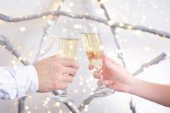 Due mani con i vetri di champagne immagini stock