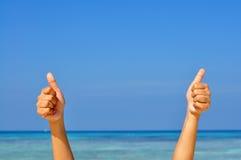 Due mani con il pollice su sul backgr del mare e del cielo blu Fotografia Stock Libera da Diritti
