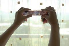 Due mani con la pellicola della foto Fotografia Stock