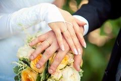 Due mani con le fedi nuziali sul mazzo della sposa Fotografie Stock Libere da Diritti