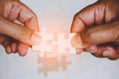 Due mani degli uomini che collegano i pezzi delle coppie di puzzle bianco Fotografia Stock Libera da Diritti