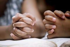 Due mani della bambina hanno piegato nella preghiera su una bibbia santa Fotografia Stock