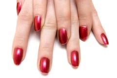 Due mani della donna con i chiodi rossi Immagine Stock