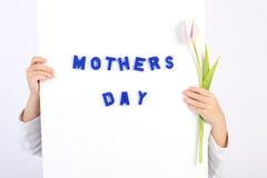 Due mani di infanzia che tengono bordo bianco con del testo un di madri blu il giorno e tulipano bianco e viola Immagini Stock