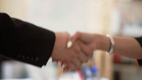 Due mani di scossa del primo piano delle signore di affari nell'accordo stock footage