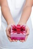 Due mani femminili che tengono scatola del presente Immagini Stock