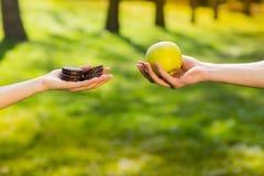 Due mani, femminili e maschii, tenenti e confrontanti biscotto e mela Fondo del parco verde fotografia stock