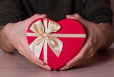 Due mani maschii che tengono il contenitore di regalo rosso nella forma di cuore Fotografie Stock