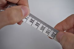 Due mani maschii che tengono una lunghezza di misurazione di misura di nastro in centimetri e metri Fotografia Stock Libera da Diritti